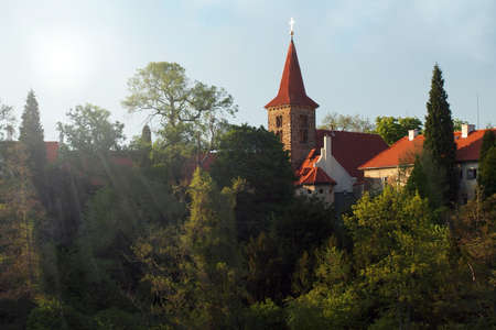 Photo of Pruhonice chateau surrounded by trees backlit by sun