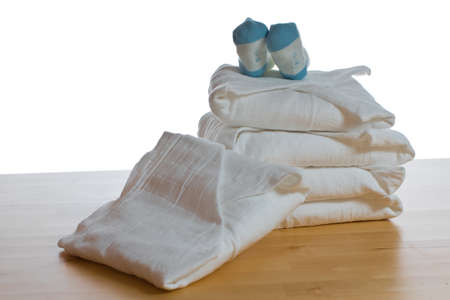 Stack of classical square white cloth diapers with blue socks on white background - with clipping path photo