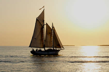 A sailboat full of people is sailing into the sunset before a yellow sky. Stock Photo - 10575816