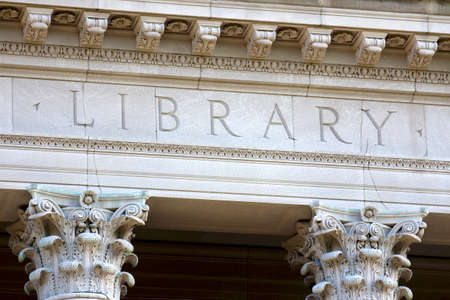 Architectural detail of a university library building, showing the letters library chiselled into its limestone