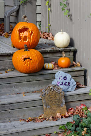 Assorted Halloween decorations guarding the front steps of a New England house.