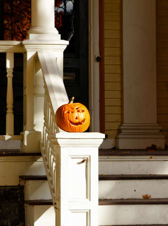 A carved Halloween pumpkin on the front steps of a New England house in Cambridge, MA
