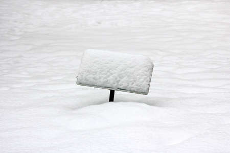 A crooked, snow-covered sign sticking out of a field of snow. Stock Photo
