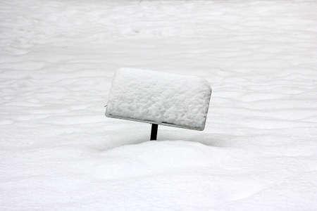 eiszeit: Ein schiefes, schneebedeckte Schild ragte aus einem Feld von Schnee.