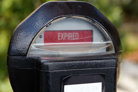 Close-up of an old-fashioned expired coin-operated parking meter. photo