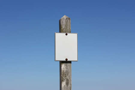A white, empty sign on a weathered wooden signpost before a clear blue sky. Stock Photo