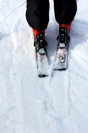 Legs of a skier with black ski pants and red ski boots on the slopes, seen from behind. Stock Photo