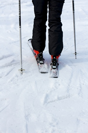 black ski pants: Legs of a skier with ski sticks, black ski pants and red ski boots on the slopes, seen from behind. Stock Photo