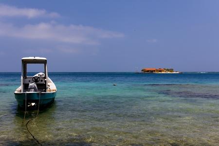 millonario: Un peque�o barco anclado en el primer plano, con una peque�a isla caribe�a visible en el fondo de las Islas del Rosario, cerca de Cartagena de Indias, Colombia Foto de archivo