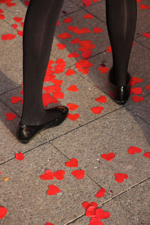 A womans lower legs as she walks on sprinkled hearts at a wedding.