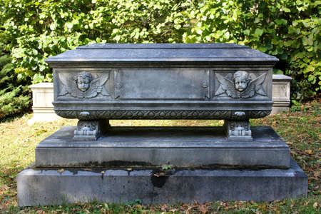 A stone memorial in the shape of a casket, adorned with the faces of two cherubim.