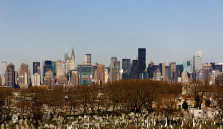 The iconic Manhattan skyline forms a backdrop to Maple Grove Cemetery in Brooklyn under a clear spring sky Stock Photo - 12583228