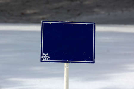 Empty blue informational sign before a snowy white background on the ski slopes.