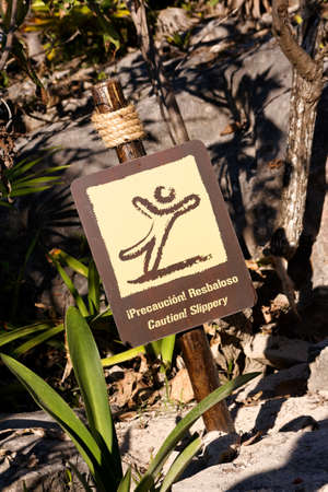 steep cliffs sign: Dual language sign in tropical surroundings warning of slippery ground. Stock Photo