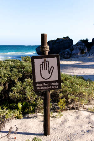 denying: Sign denying access to a beautiful Caribbean beach in English and Spanish (portrait format). Stock Photo