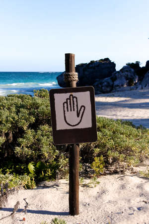 Brown and tan sign showing a hand pictogram at a beautiful Caribbean beach (portrait format) photo