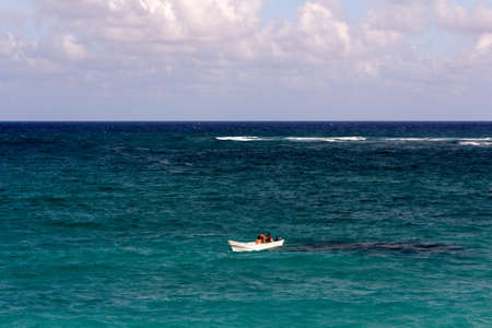 Tiny white boat with three people in it alone on a vast caribbean sea.