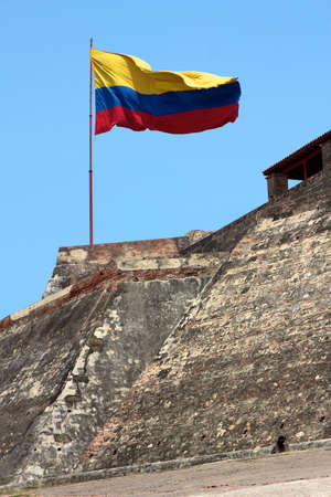 A Colombian flag is streaming in the wind over the weathered walls of the fortress of Castillo San Felipe de Barajas in Cartagena de Indias, Colombia. photo