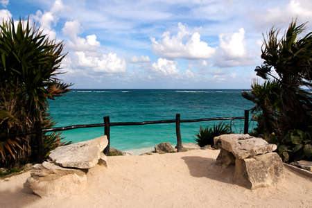 cancun: Two stone Benches overlook the turquoise ocean at the Mayan archeological zone of Tulum, Quintana Roo, Mexico.