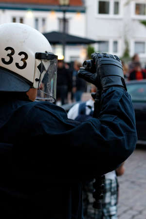 HAMBURG, GERMANY - MAY 1, 2012: Police officer in full riot gear films violent protesters during a May Day demonstration in Hamburg, Germany on May 1, 2012.