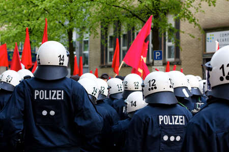 HAMBURG, GERMANY - MAY 1, 2012: Police officers in full riot gear face protesters during the May Day demonstration in Hamburg, Germany, on May 1, 2012.