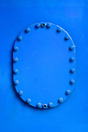 A bolted cover on a ship, painted in vibrant blue