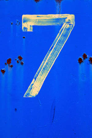 The number 7  seven  painted in faint yellow on a vibrant blue background at an industrial facility  Stock Photo - 14274007