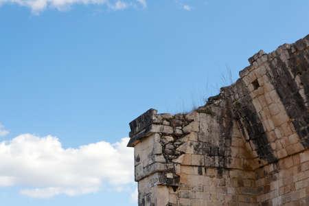 Detail of a crumbling Mayan ruin before the blue sky at Chichen Itza, Yucatan, Mexico  photo