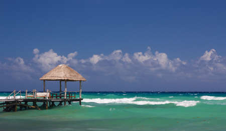 Wooden jetty leading into the perfect turquoise waters at a Caribbean beach
