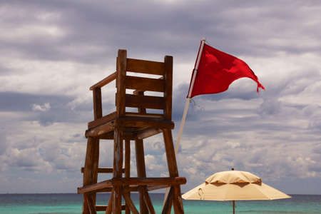 lifeguard: Abandoned lifeguard chair at a Caribbean beach, with the horizon over the ocean in the background and a red flag showing unsafe conditions, under a cloudy sky