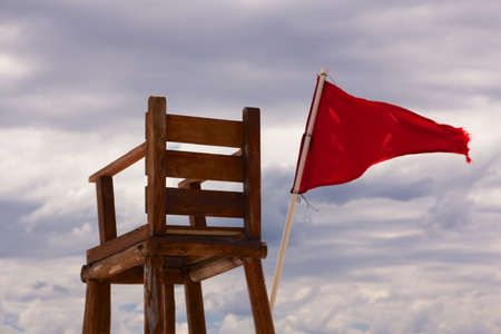 Lifeguard chair sitting empty with a red flag streaming in the wind, showing unsafe conditions for swimming, before the background of an overcast sky  Stock Photo