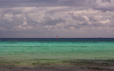 Sailboat before the horizon under a cover of clouds on the Caribbean ocean  photo