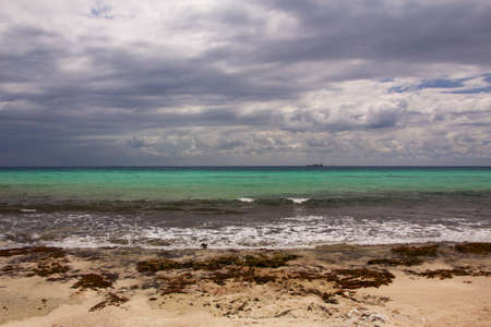Panoramic view of the surf on a natural tropical beach in the Caribbean under a cover of clouds  Stock Photo
