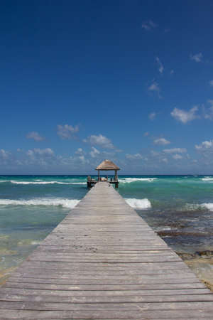 perfect waves: Wooden jetty leading into the perfect turquoise waters at a natural Caribbean beach
