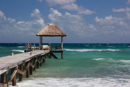 Wooden landing leading into the turquoise Caribbean waters at a Mexican beach