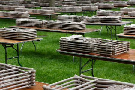 Tables and Chairs neatly stacked on a lawn at Harvard Yard, waiting for people to use them at an event  Stock Photo