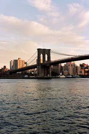 The Brooklyn Bridge rises before the Brooklyn skyline, seen from Lower Manhattan in New York, NY, USA. photo