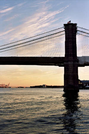 reddening: Silhouette of New York Citys Brooklyn Bridge contrasted against the reddening horizon in the evening.