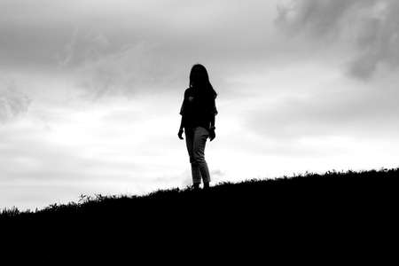 grassy knoll: Silhouette of girl standing on a grassy hill slope against an overcast sky.