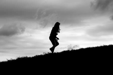 Silhouette of girl running up a grassy hill slope.