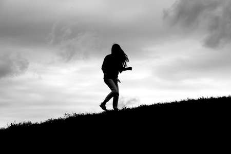 grassy knoll: Silhouette of girl turning towards the viewer on a grassy hill slope.