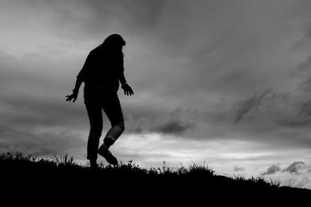 grassy knoll: Silhouette of girl walking away on a grassy hill slope. Stock Photo