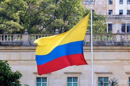 The Colombian flag streaming before a bright, cloudless sky.
