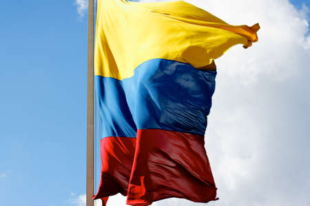 billowing: The yellow, blue and red of the Colombian flag billowing in the wind towards the camera.