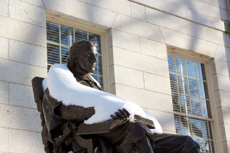 dormitories: Harvard University campus famous John Harvard Statue on the day after a blizzard, half covered in snow.