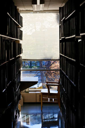 stark: A quiet, secluded workplace at a university library, dark before stark bright light through a window  Stock Photo
