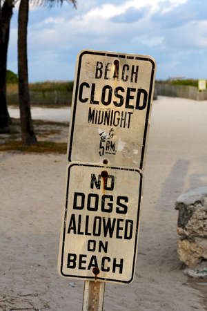 closure: Signs at South Beach, Miami, FL, USA, announcing beach closure times and a ban on dogs. Stock Photo