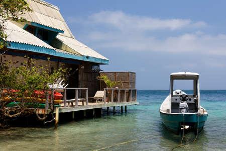 House and Boat in a Lagoon in the Caribbean Islas del Rosario near Cartagena de Indias, Colombia. Stock Photo