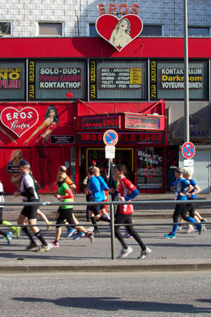 reeperbahn: April 21, 2013 - Hamburg, Germany: Marathoners pass by the brothels and strip clubs of Hamburgs infamous red light district at the Reeperbahn on April 21, 2013, in Hamburg, Germany.