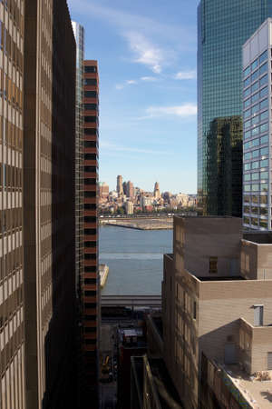 manhattans: View through a canyon of high-rises from Manhattans downtown Financial District towards the Brooklyn shoreline in New York, NY, USA.